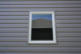 Gray Vinyl Siding and installed window without Trim Work in MA by Marshall Building and Remodeling