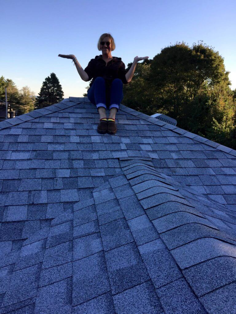 Woman Sitting on New Roof Installed by Marshall Building & Remodeling